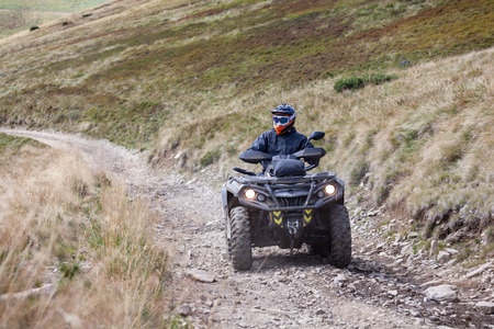 Front view of quad bike zipping along a country road in Carpathian mountains, Ukraine. Imagens
