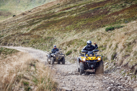 Front view of quad bikes zipping along a country road in Carpathian mountains, Ukraine.