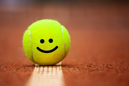 Smiling emoji on tennis ball lies on the clay court close up.