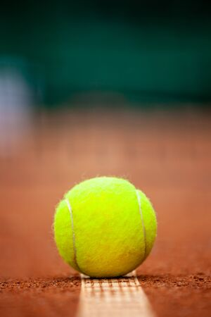 Yellow tennis ball lies on the clay court close up.