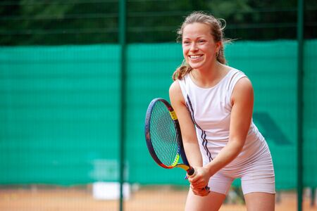 Happy female tennis player holding the racket in ready position.