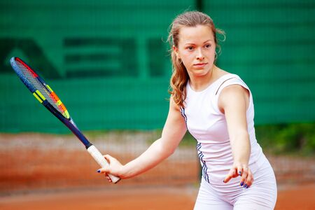 Young beautiful female tennis player playing tennis.