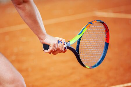 Close up female tennis player hitting two-handed backhand.