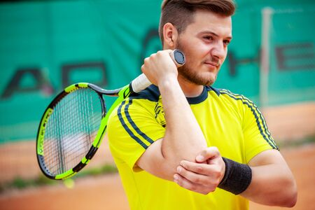 Male tennis player holding his injured elbow. Tennis elbow concept.