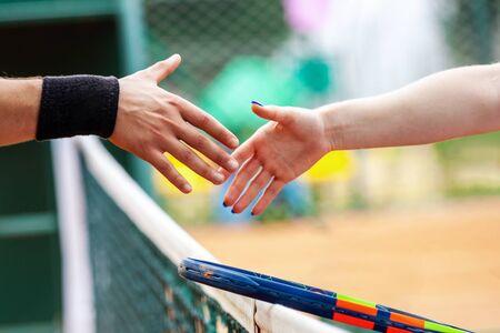 Tennis players shake hands after match closeup.