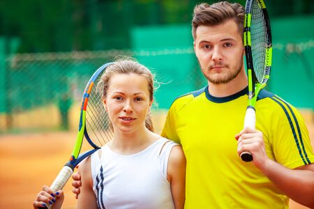 Portrait of two tennis players posing looking at camera.