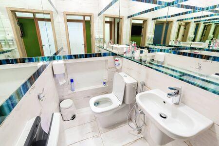 Modern public empty restroom with washstand mirror. 免版税图像