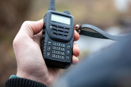Close up of male holding walkie talkie.