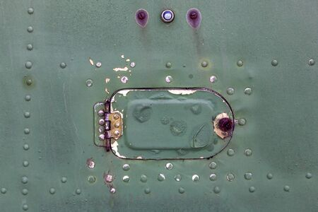 Close up of old aircraft green painted aluminum hatch with rivets. 免版税图像