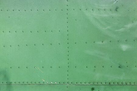 Close up of old aircraft green painted aluminum texture with rivets.