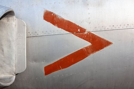 Close up of old aircraft aluminum panel with red arrow. Stock Photo
