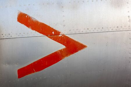 Close up of old aircraft aluminum panel with red arrow. 免版税图像