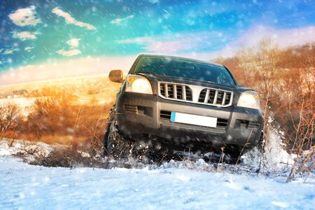 Front view of Offroad car climbing winter hill. Winter travel concept.
