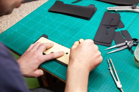 Leather Craftsman working with leathet. Making a wallet. 免版税图像