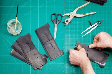 Top view of Leather Craftsman working with leathet. Making a wallet.