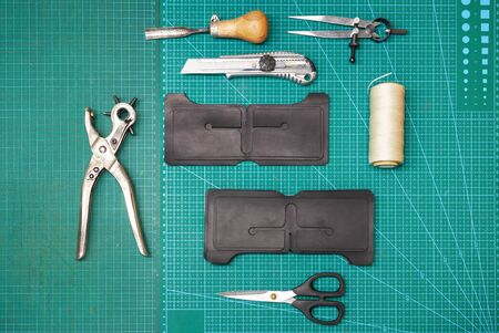 Top view of Leather work tools and a piece of leather.