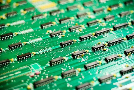 Rows of microchips on a large green circuit board with shallow depth of field