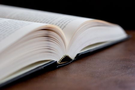 Hardcover book opened on a leather desk