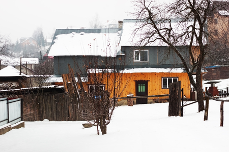 A snowy winter scene of a small house in the heart of Yaremche