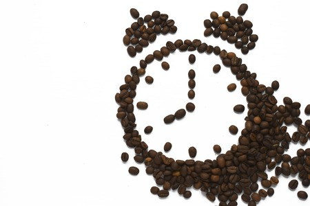 Alarm clock 8 AM arranged from roasted coffee beans. Time to awake drink espresso isolated on white background Imagens - 121045272