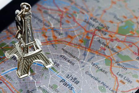 Eiffel Tower keychain on a Electronic Map of Paris Standard-Bild