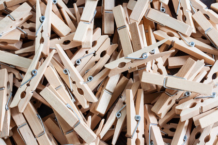 wooden clothespins piled on the floor and dark wood.