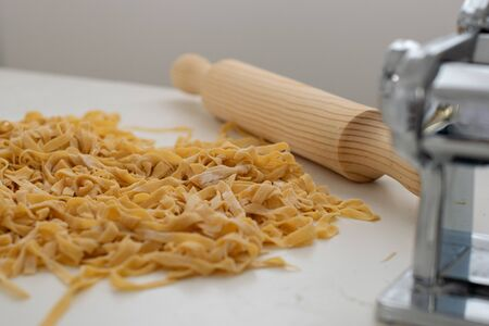 tagliatelle on the table, near rolling pin an machine ready to cook Banque d'images