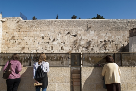 monotheism: Women looking at the wailing wall through a fence Editorial