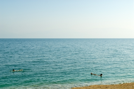 A view of the Dead sea from Israel side. There are two persons floating on the water. The water is dense and turquoise color photo