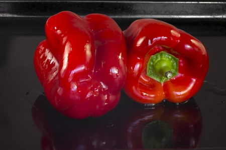 be soaked: Two red peppers soaked in oil ready to be tucked into the oven and roast  They are on a tray with a few drops of oil Stock Photo