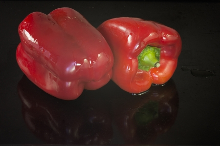 be soaked: Two red peppers soaked in oil, ready to be tucked into the oven and roast  They are on a black background with a few drops of oil