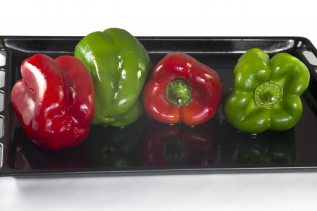 be soaked: Four peppers, two red and two green, soaked in oil, ready to be tucked into the oven and roast  They are on a black tray with a few drops of oil