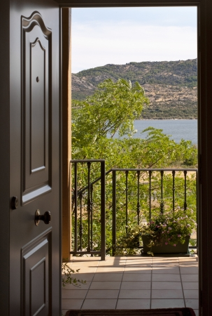 Can see the open door of a home with a balcony and a lake in the background. It is a house in a rural environment and transmits tranquility and peace. photo