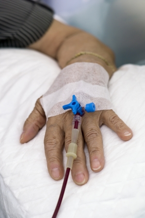 intravenously: It can be seen a hand of an elderly woman with a stopcock for entry of fluid intravenously. The woman is being subjected to a blood transfusion. Just part of the hand is on focus. Can see the blood through the catheter