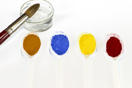 pigments:  Powdered pigments on white Teaspoons  There is a little bowl with water and a brush  The pigments are blue, yellow, red and ocher