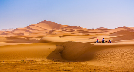 sandhills: Saara dunes and a group of people using camels as transportation through the valleys of the dunes.