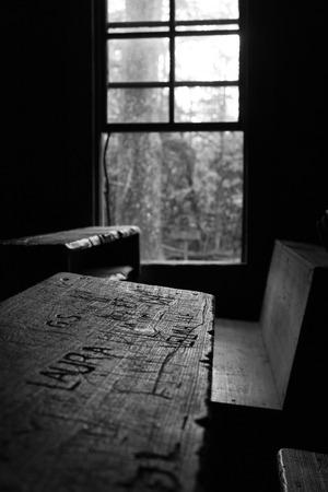 niños abandonados: banco de la escuela vieja en el edificio del edificio escolar abandonado en el interior del parque nacional de las montañas ahumadas en los Estados Unidos. Todavía tiene los nombres de los niños grabadas en su superficie. Foto de archivo