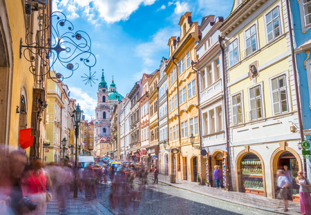 The street after the Little Quarter Bridge Tower, Prague, Czech Republic, with the St. Nicholas Church in the background. Stock Photo