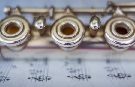 flute key: Transversal flute music instrument detail, over a music sheet.