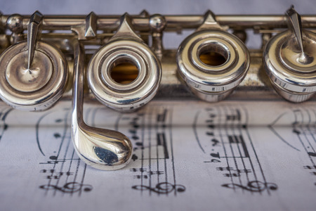 flute key: Transversal flute instrument detail, over a music sheet. Stock Photo