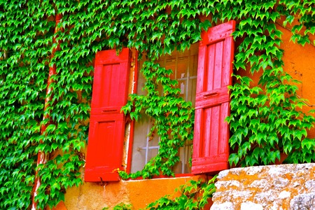 roussillon: Vibrant shutters on the ivy exterior of a villa in Roussillon, France
