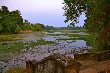 flowing river: Stone steps down into a gently flowing river in Kerala, India