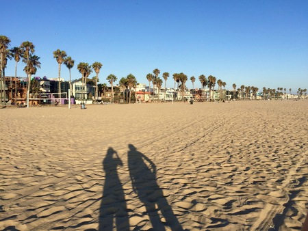 documenting: Picture of the shadows of two tourists creatively documenting their vacation to Venice Beach, California Stock Photo