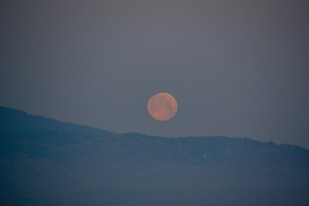 approaches: A full moon sinking from view behind the Pirin Mountains outside of Melnik, Bulgaria as dawn approaches Stock Photo