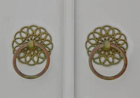Ornate door handles on a historic home on the island of Hydra, Greece. Stock Photo