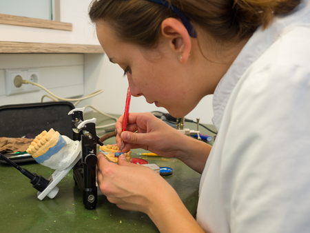 Female dental technician working on a wax crown Stock Photo