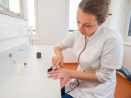 Female dental technician attaching a wax crown in a muffles