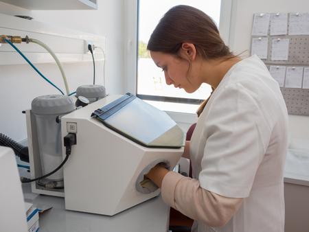 Female dental technician working with a sandblasting machine