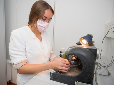 Female dental technician polishing a tooth crown Stock Photo