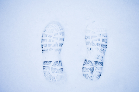 Two foot prints in the snow, cold and winter